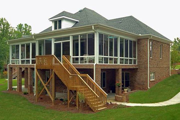 A sunroom extending a 2nd floor or raise house designed with the overall house design in mind with high quality materials that naturally extende the house into the outdoors